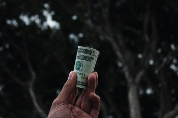 A man holding a bundle of cash in his hands with trees in the background