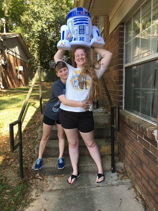 Devon and Lindsey pose with Star Wars shirts and a stuffed R2-D2