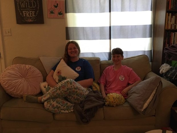 Devon and Lindsey sit on their couch with matching pajamas