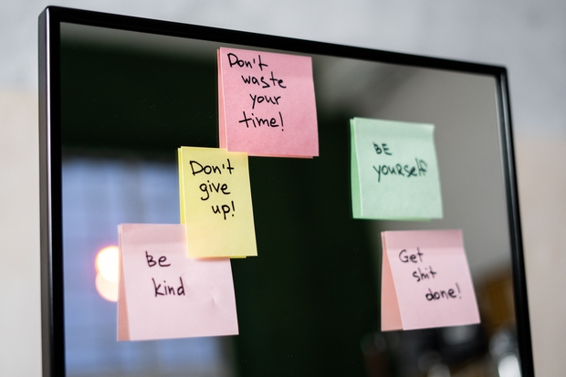 sticky notes with words on a mirror