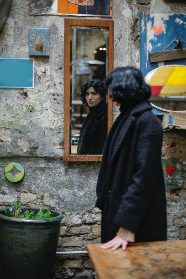 women in black coat near a brown wooden table looking in a mirror on the wall