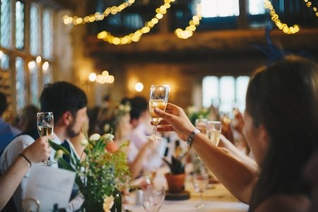 People raising champagne glasses at a wedding party