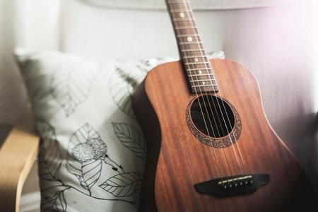 A brown guitar sitting on a white chair with a pillow.