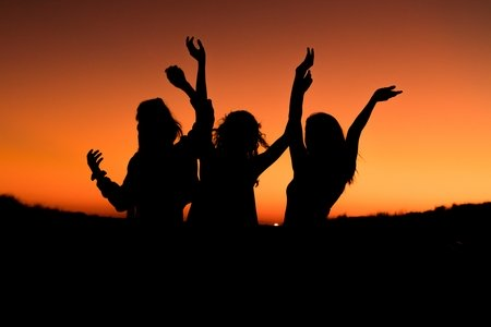 silhouette of three women with hands up