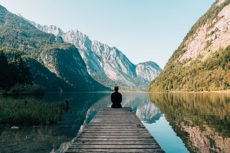 man sitting on gray dock looking out over a lake and mountains