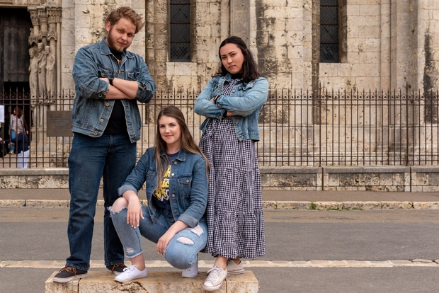 Three people posing in front of a church