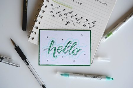 green and white Hello board decor on top of notebook with handwritten lettering framed by brush pens