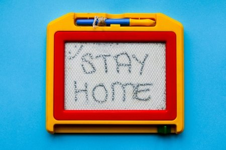 """""""Stay home"""" written on an etch-a-sketch"""