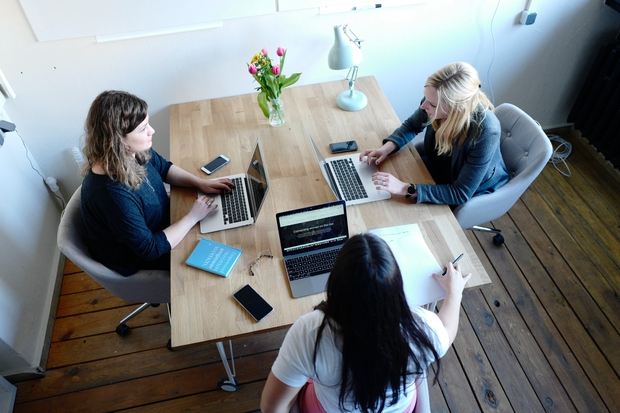 3 women working on computer at table