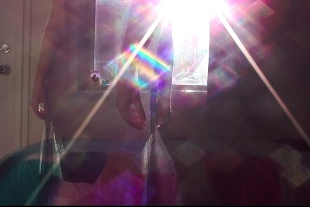 Screenshot from my own film, silhouettes of woman in the light with rainbow image.