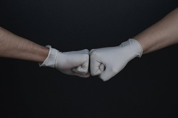 hands with gloves on fist bumping