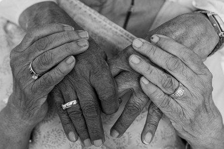 grayscale photo of old couple holding hands
