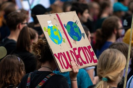 """demonstration for climate change action - sign that says """"You decide"""" with one clean earth and one dirty earth"""