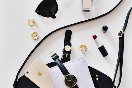 Women's sunglasses and a black bag with watch and iPhone 6