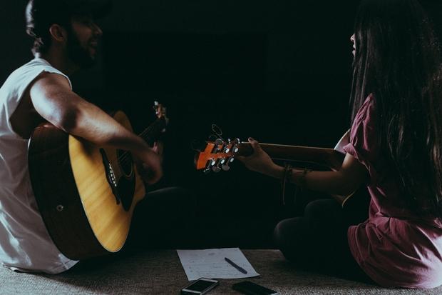 man & woman singing & playing guitar