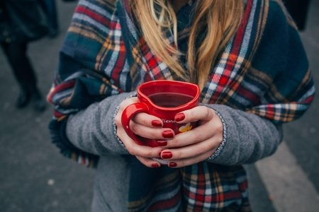 Red nails, woman holding tea, plaid scarf