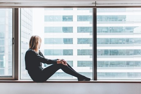 Woman sitting on a white window sill looking out into the distance
