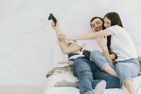 man and woman on a bed fighting over a video game controller