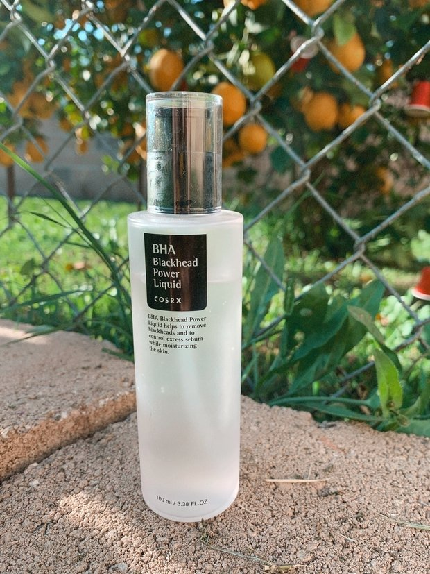 skincare product in front of a lemon tree