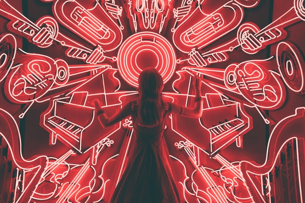 woman standing in front of neon music wall