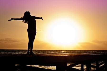 women with arms wide open at the beach sunset