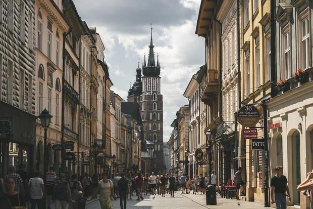 People walking down a street lined with buildings in Krakow, Poland