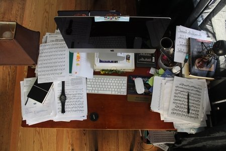 Messy desk with a computer and sheet music