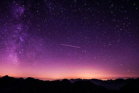 silhouette photo of mountain during night time, purple sky with shooting star