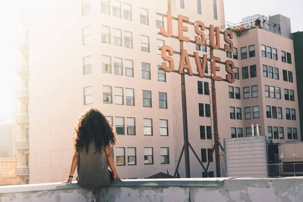 woman in gray top sitting on a building's edge in front of