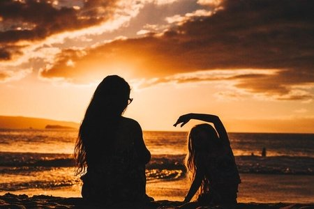 mother and daughter sitting on the beach in front of a sunset