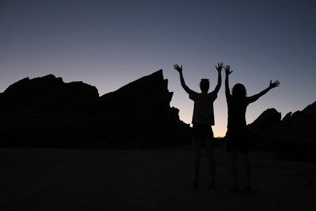 silhouette of two people and rocks