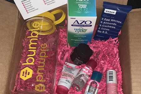 box with pink confetti and products from Garnier, Bumble, Innisfree, Azo, RXBar, and CoverGirl