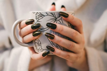 woman with black monochrome manicure holding a black and white patterned mug