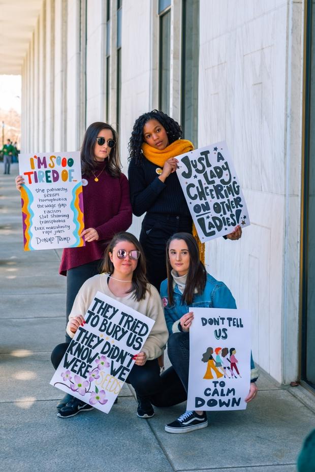 Four women holding feminist posters