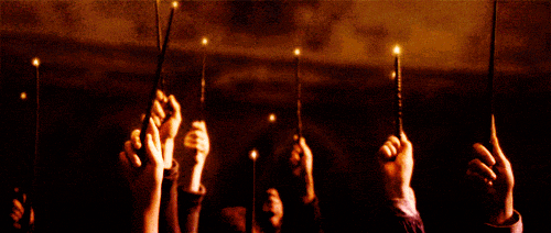 Hogwarts students raising wands with lights