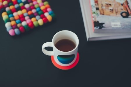 Coffee mug on table with books and colorful pot holder