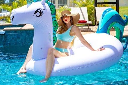 girl in bikini bathing suit in pool on unicorn floatie in summer