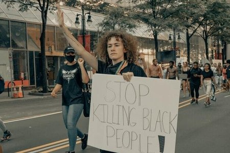 "Protester holding sign that says ""stop killing black people"""