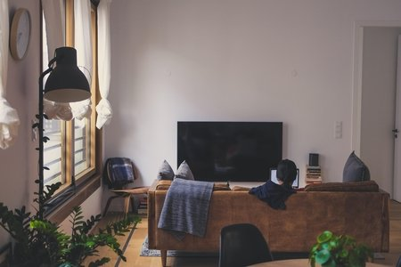 Woman uses laptop on couch in a nice apartment