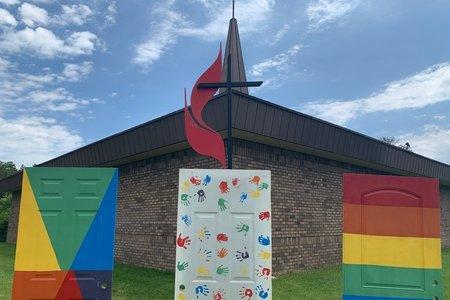Rainbow painted doors in front of metal cross