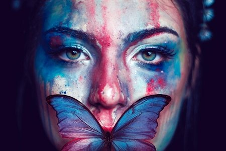 Colorful butterfly and paint on woman's face