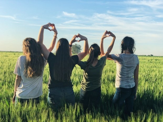 4 women holding up hearts in a field