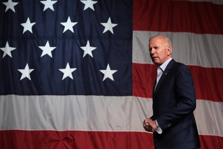 Joe Biden speaking in front of an American flag