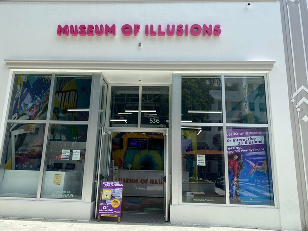 Entrance to Museum of Illusions, white building with pink letter title.