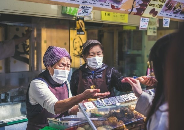 two japanese women wearing masks working at a storefront interacting with customers