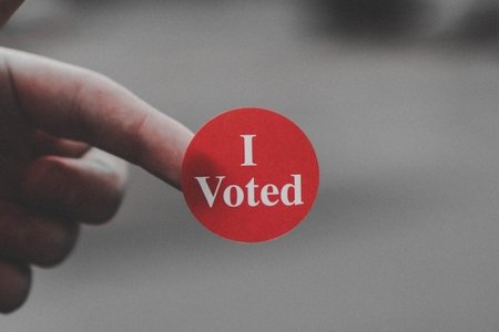 "Hand holding a red sticker with the words ""I Voted"""