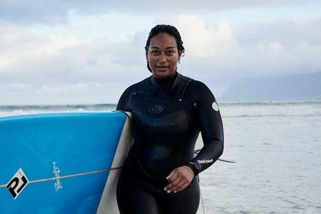 Aaniyah Omardien walking out of the sea with her surfboard.