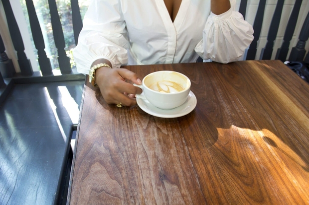 woman sitting at a wooden table and holding a latte