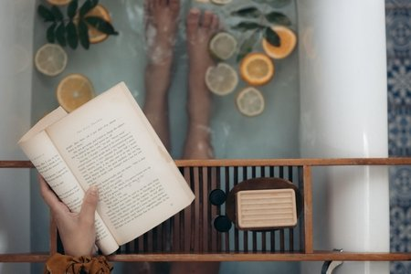 person holding book in a bath