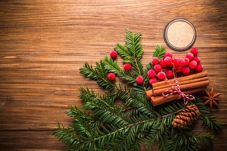 pine leaves, holly, a bundle of cinnamon, and a pinecone on a wooden table